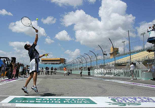 Indycar driver Helio Castroneves plays tennis with ATP tennis player David Nalbandian on the front stretch of the Homestead-Miami Speedway at the...