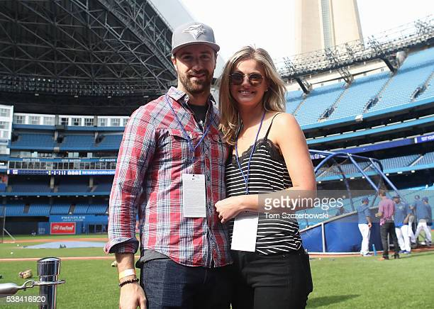 IndyCar driver James Hinchcliffe and his girlfriend pose for a photo during batting practice prior to the start of the Toronto Blue Jays MLB game...