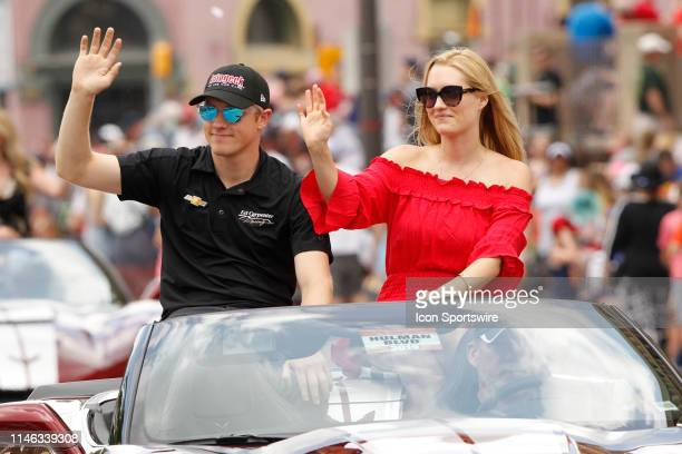 IndyCar driver Spencer Pigot of the AutoGeek Ed Carpenter Racing Chevrolet and girlfriend Katie Bell wave to the crown during the 500 Festival Parade...