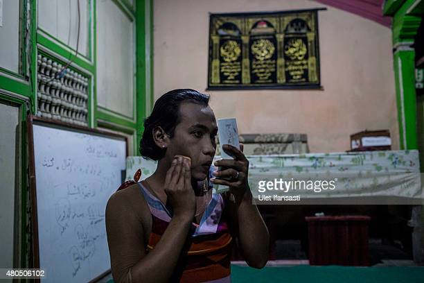 Inez, a member of a Pesantren boarding school, Al-Fatah, for transgender people known as 'waria' applies make-up to her face during Ramadan on July...