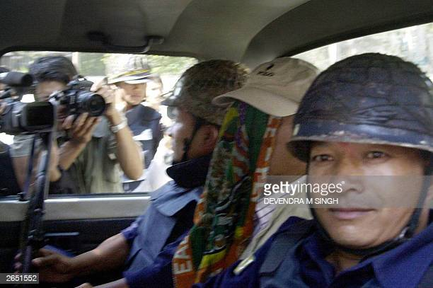 Infamous international criminal Charles Sobhraj covers his face while leaving Hauman Dhoka jail in Kathmandu on his way to court, 10 October 2003....