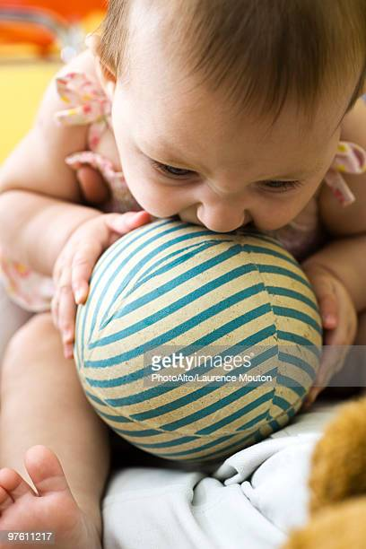 infant chewing on striped ball - bent over babes stock pictures, royalty-free photos & images