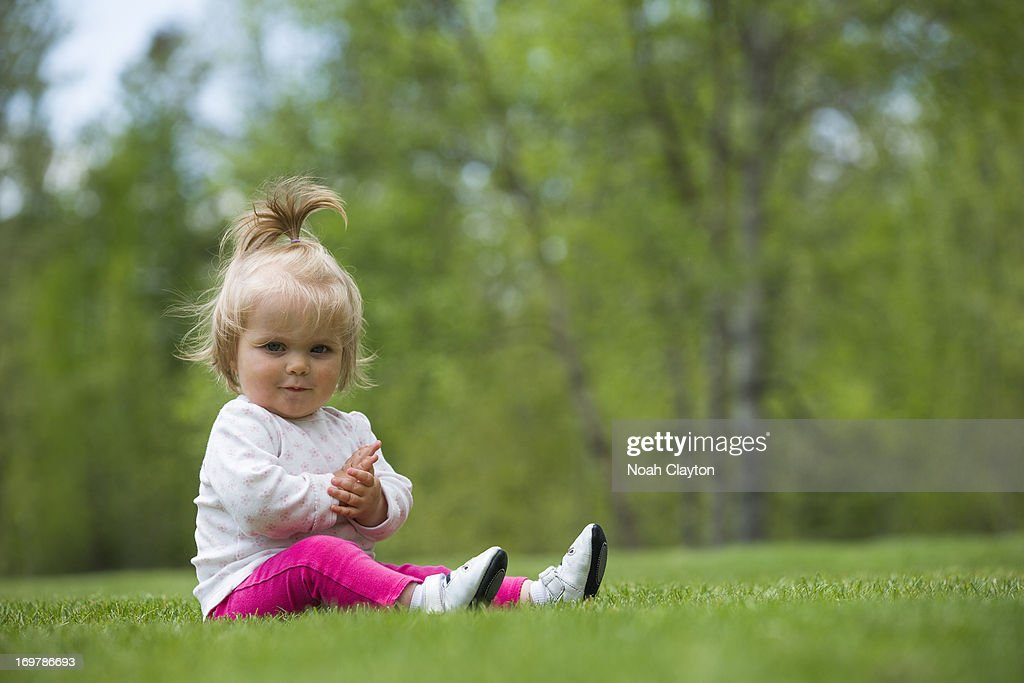 Infant girl sits in yard and looks at viewer : Stock Photo
