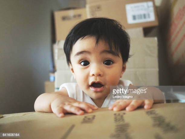 infant inside one of the boxes as the family is moving house