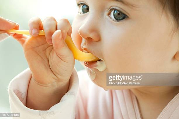 infant learning to eat with a spoon - vida de bebé fotografías e imágenes de stock
