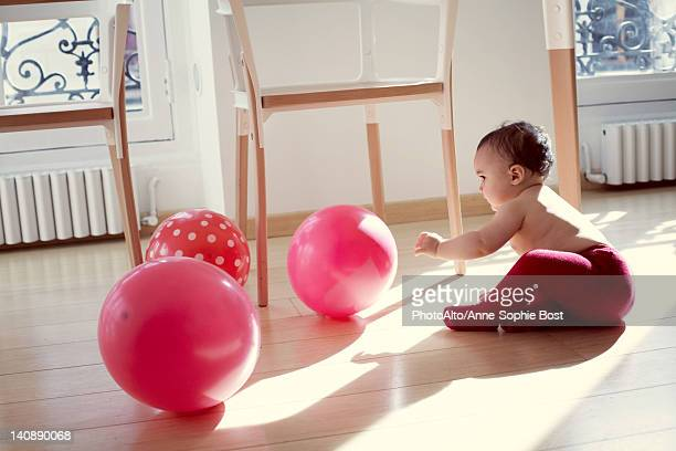 Infant playing with ballons