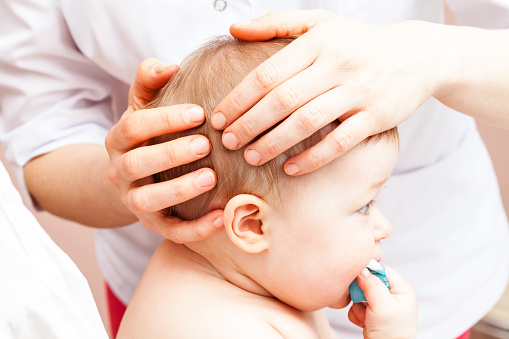 Infant receiving osteopathic treatment of her head 856740272