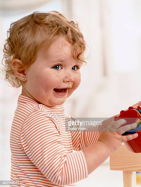 Infant Wearing a Striped Top Playing with Toys