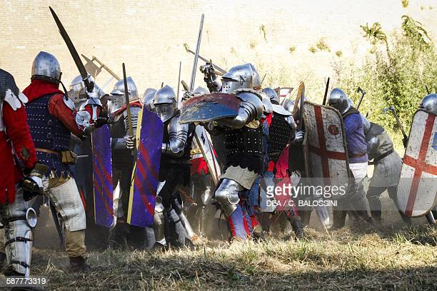 Infantry and cavalry of opposing armies engaged in battle armed with swords and axes, end of 14th century. Historical reenactment.