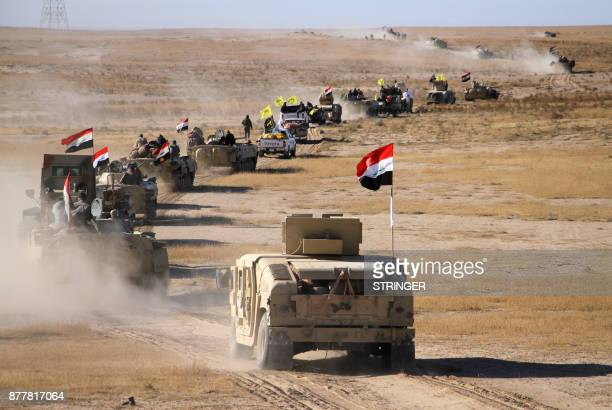 Infantry fighting vehicles and humvees of the Iraqi forces supported by members of the Hashed alShaabi advance in the western desert in the northern...