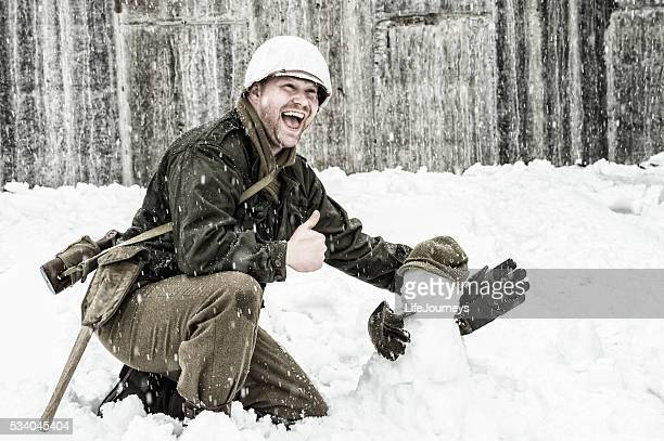 wwii us infantry man building a snowman and laughing - 20th century stock pictures, royalty-free photos & images