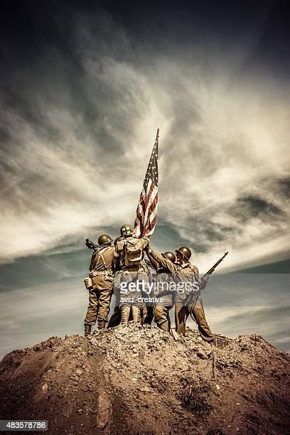 wwii infantry squad hoists flag on hill - army soldier stock photos and pictures