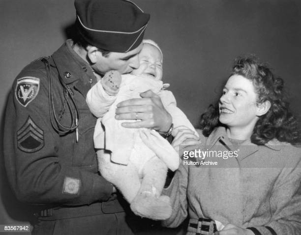 US infantryman George M Deal greets his English wife Yvonne and their baby son Adrian on their arrival from London at La Guardia Airport New York...
