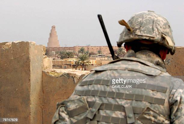 Infantryman takes cover as he keeps watch across the rooftops of the Iraqi city of Samarra on February 11, 2008. Appearing in the background is the...