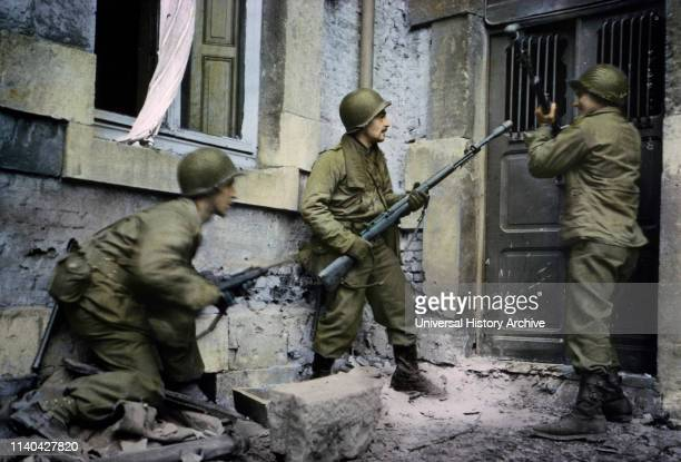 Infantrymen Battle Down Door of House where German Snipers are Holding Out Stavelot Belgium ArdennesAlsace Campaign Battle of the Bulge December 1944
