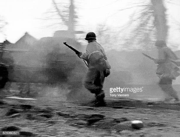 US Infantrymen follow in the wake of a tank during fighting near Hemmerden Germany as part of the Allied push to the Rhine World War II 28th February...
