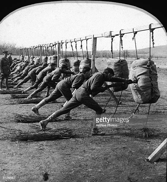 US infantrymen known as 'doughboys' practice 'the short point stab' using bayonets on dummies as part of their combat training 1910s