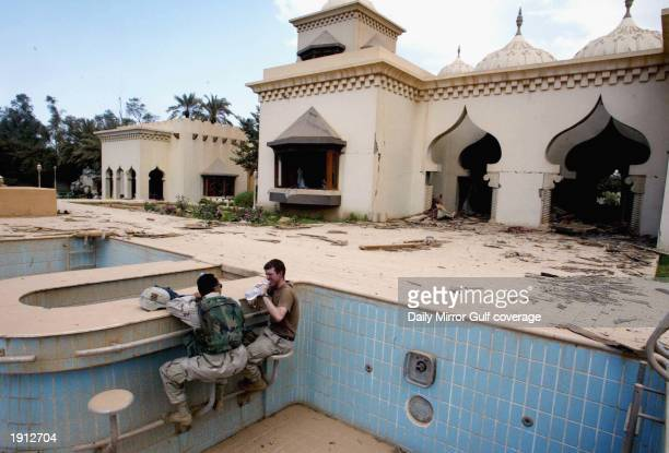 US infantrymen sit by the pool bar at Uday's the playboy son of Saddam Hussein palace April 10 2003 in Baghdad US warplanes fired six satelliteguided...