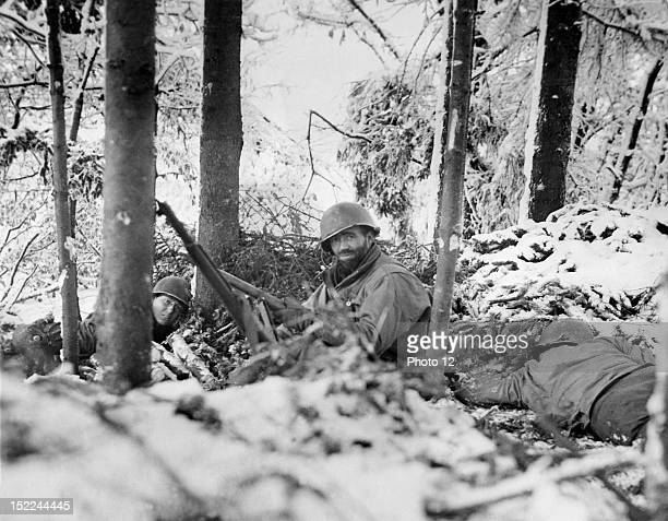 US infantrymen take cover from enemy artillery fire in a snowblanketed Luxembourg wood during the Battle of the Bulge