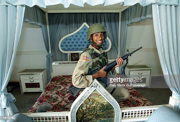 US infantrywoman Felicia Harris poses for a picture as she lays in the four poster bed at the palace of Uday the playboy son of Saddam Hussein April...