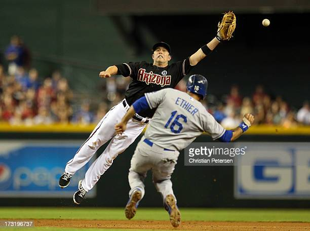 Infielder Aaron Hill of the Arizona Diamondbacks leaps as he attempts to catch an errant throw over the sliding Andre Ethier of the Los Angeles...