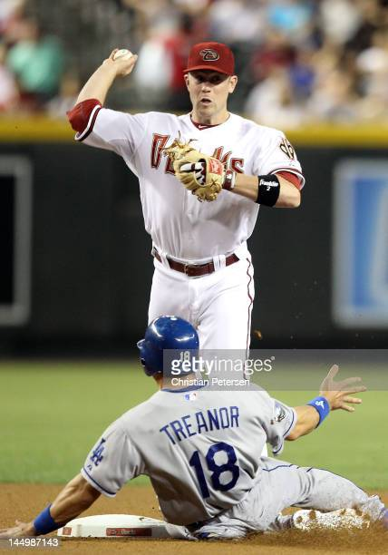 Infielder Aaron Hill of the Arizona Diamondbacks throws over the sliding Matt Treanor of the Los Angeles Dodgers as he attempts an unsuccessful...
