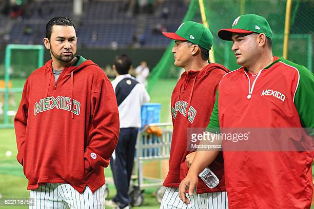 Infielder Adrian Gonzalez of Mexico talks with Head coach Edgar Gonzales and Coach David Gonzalez Jr during a practice session prior to the...