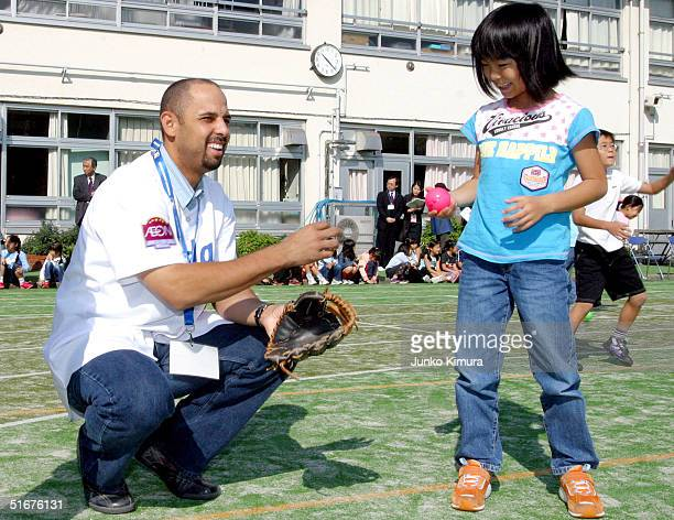 Infielder Alex Cora of the Los Angeles Dodgers gives a ball to a Japanese student during a baseball clinic held at Hatomori Elementary School on...