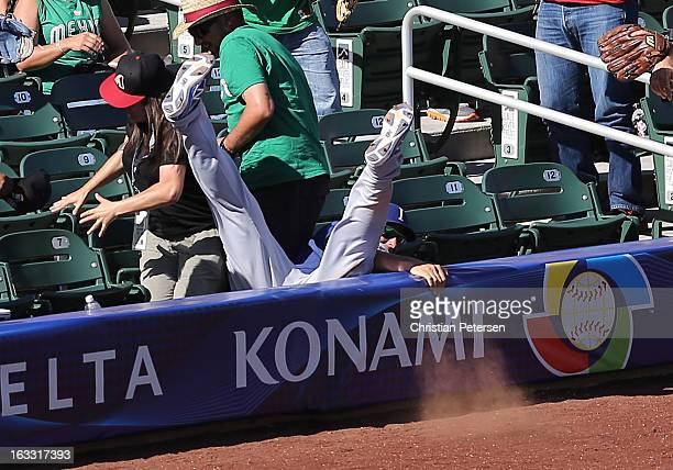 Infielder Alex Liddi of Italy falls into the seats as he attempts to catch a fly ball during the World Baseball Classic First Round Group D game...