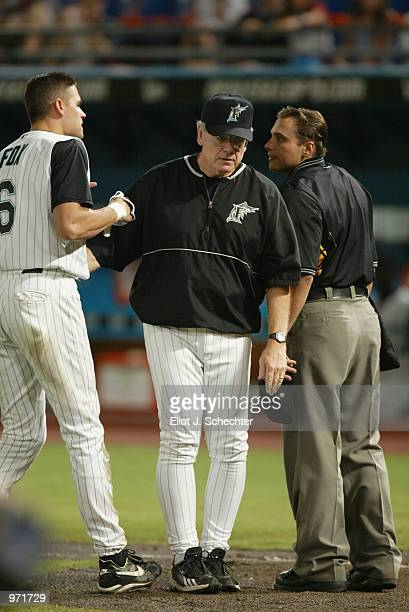 Infielder Andy Fox of the Florida Marlins is held back by manager Jeff Torborg as he argues with the umpire against the New York Mets during the game...
