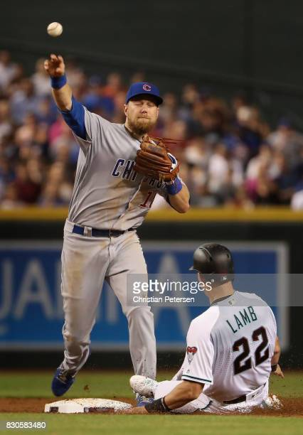 Infielder Ben Zobrist of the Chicago Cubs throws over the sliding Jake Lamb of the Arizona Diamondbacks to complete a double play during the first...