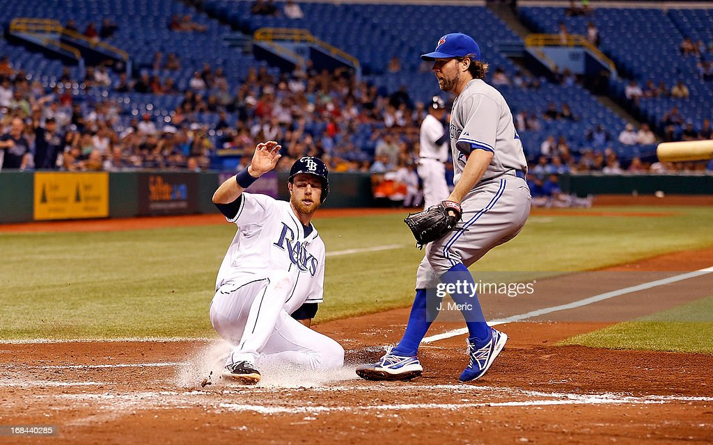 Infielder Ben Zobrist #18 of the Tampa Bay Rays slides home on a wild pitch as pitcher R.A. Dickey #43 of the Toronto Blue Jays looks on during the game at Tropicana Field on May 9, 2013 in St. Petersburg, Florida.