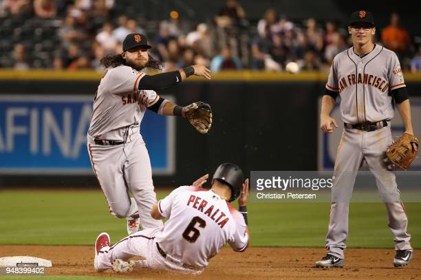 Infielder Brandon Crawford of the San Francisco Giants throws over the sliding David Peralta of the Arizona Diamondbacks to compete a double play...