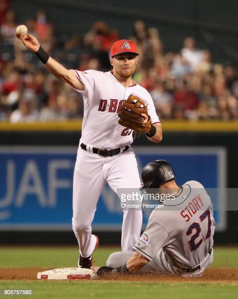Infielder Brandon Drury of the Arizona Diamondbacks throws over the sliding Trevor Story of the Colorado Rockies to complete a double play during the...