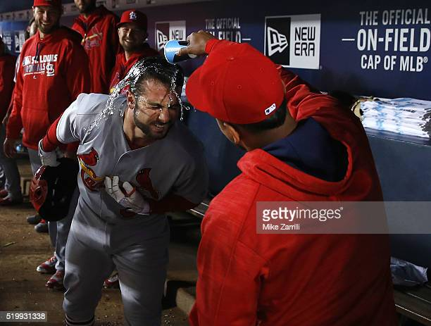 Infielder Carlos Martinez of the St Louis Cardinals dumps water on pinch hitter Greg Garcia after Garcia's ninth inning home run during the game...
