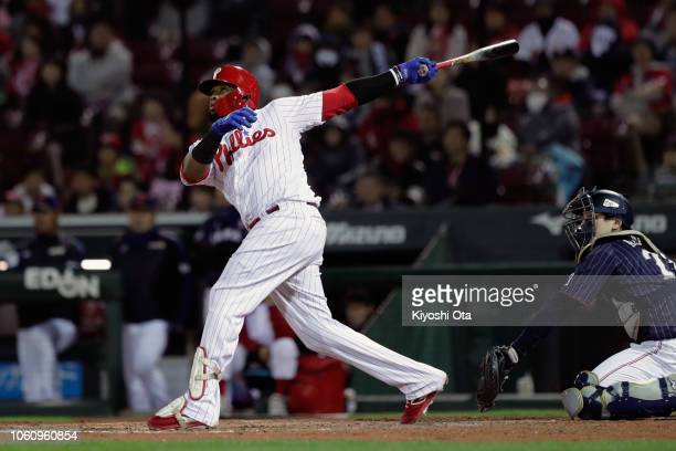 Infielder Carlos Santana of the Philadelhia Phillies hits a sacrifice fly to make it 31 in the bottom of 8th inning during the game four between...