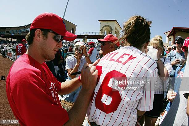 Infielder Chase Utley of the Philadelphia Phillies signs a fan's jersey before MLB Spring Training pre-season game against the Cleveland Indians at...