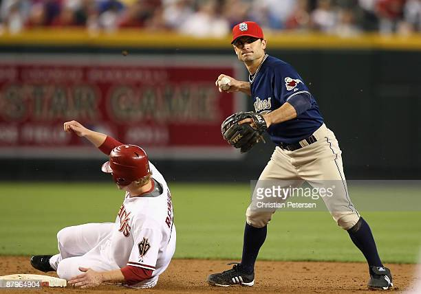 Infielder Chris Burke of the San Diego Padres gets the force out on Mark Reynolds of the Arizona Diamondbacks at second base during the major league...
