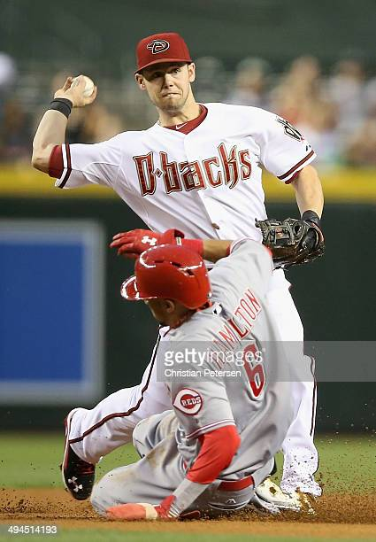 Infielder Chris Owings of the Arizona Diamondbacks throws over the sliding Billy Hamilton of the Cincinnati Reds to complete a double play during the...