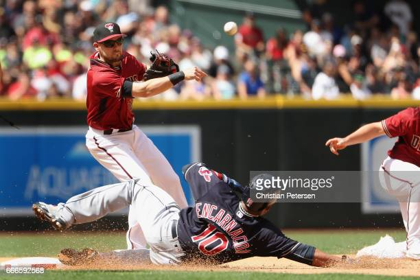 Infielder Chris Owings of the Arizona Diamondbacks throws over the sliding Edwin Encarnacion of the Cleveland Indians attempting an unsuccessful...