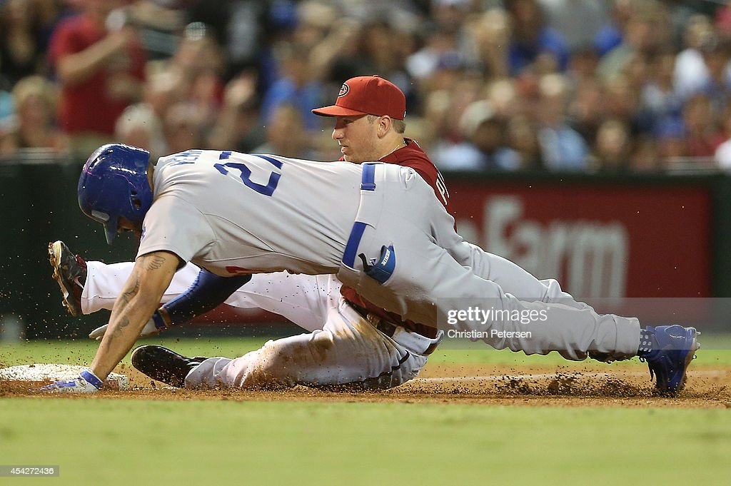 Infielder Cliff Pennington #4 of the Arizona Diamondbacks tags out Matt Kemp #27 of the Los Angeles Dodgers at he attempts to take third base after a double during the third inning of the MLB game at Chase Field on August 27, 2014 in Phoenix, Arizona.