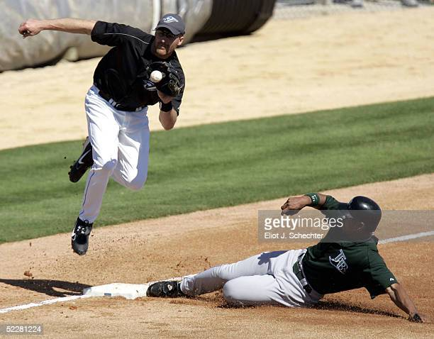 Infielder Corey Koskie of the Toronto Blue Jays is unable to tag out Chris Singleton of the Tampa Bay Devil Rays at third base on March 5 2005 at...