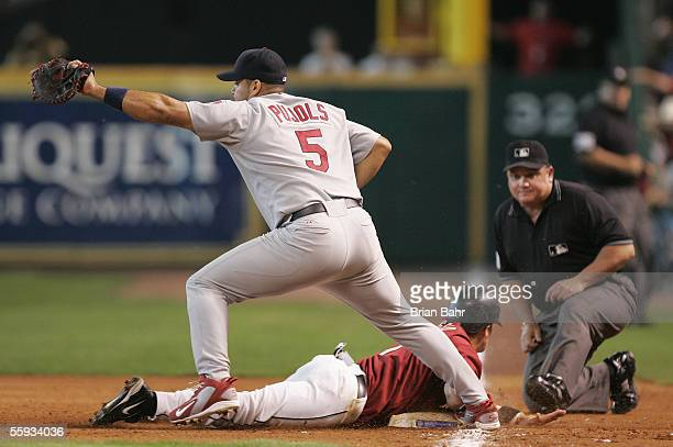 Infielder Craig Biggio of the Houston Astros slides back into first base safely under Albert Pujols of the St. Louis Cardinals during Game Four of...