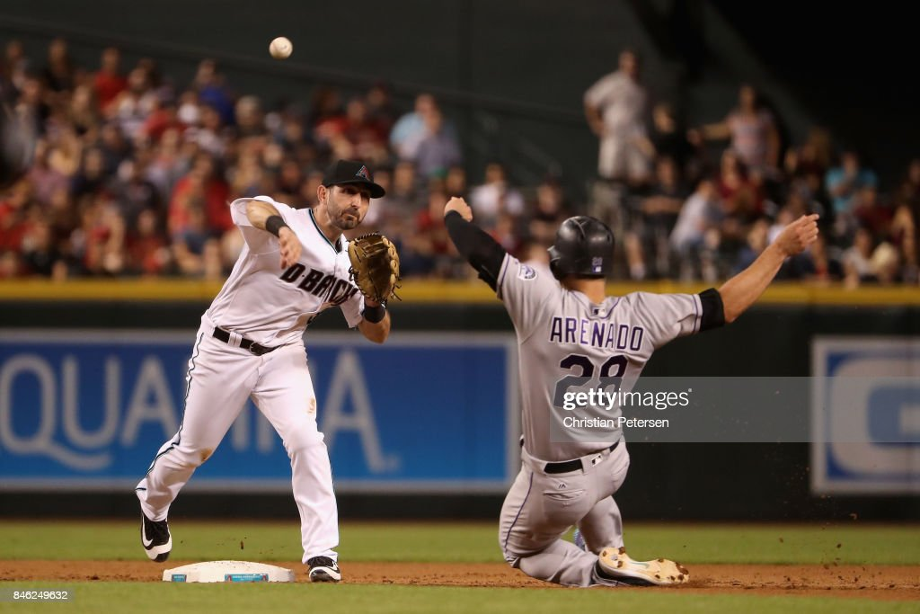Infielder Daniel Descalso #3 of the Arizona Diamondbacks throws over the sliding Nolan Arenado #28 of the Colorado Rockies attempting an unsuccessful double play during the fifth inning of the MLB game at Chase Field on September 12, 2017 in Phoenix, Arizona.
