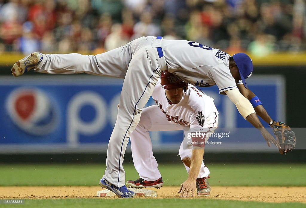 Infielder Dee Gordon #9 of the Los Angeles Dodgers falls over A.J. Pollock #11 of the Arizona Diamondbacks after completing a double to end the MLB game at Chase Field on April 11, 2014 in Phoenix, Arizona. The Dodgers defeated the Diamondbacks 6-0.