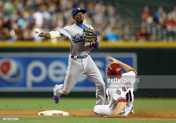 Infielder Dee Gordon of the Los Angeles Dodgers throws over the sliding AJ Pollock of the Arizona Diamondbacks to complete a double play during the...