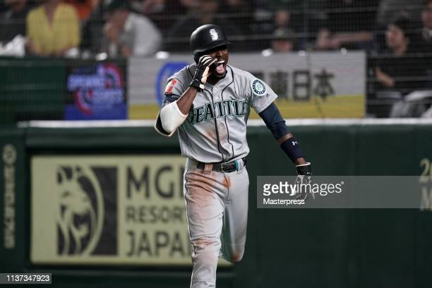 Infielder Dee Gordon of the Seattle Mariners celebrates scoring a run to make it 5-4 as Outfielder Domingo Santana grounds into force out in the 12th...