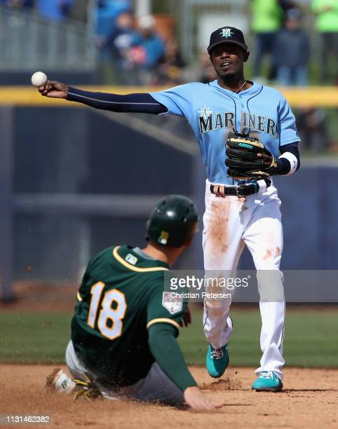 Infielder Dee Gordon of the Seattle Mariners throws over the sliding Chad Pinder of the Oakland Athletics to complete a double play during the second...