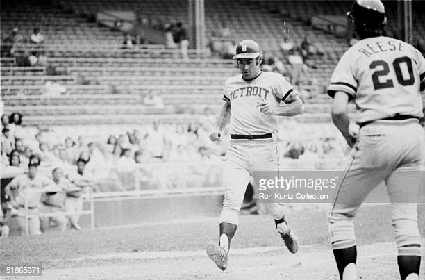 Infielder Dick McAuliffe of the Detroit Tigers touches home plate to score as teammate Rich Reese approaches to shake his hand during a game against...