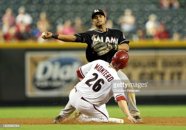 Infielder Donovan Solano of the Miami Marlins throws over the sliding Miguel Montero of the Arizona Diamondbacks attempting an unsuccessful double...